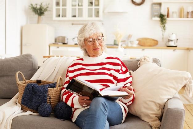 Porträt der stilvollen attraktiven rentnerin in runden brillen, die zu hause mit gutem buch entspannen. freudige ältere frau, die eine brille trägt, bestseller liest, bequem auf sofa sitzt Kostenlose Fotos