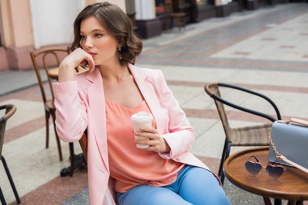 Porträt der stilvollen denkenden dame, die am tisch sitzt und kaffee im sommerstil der rosa jacke trinkt, blaue handtasche, accessoires, straßenstil, frauenmode Kostenlose Fotos