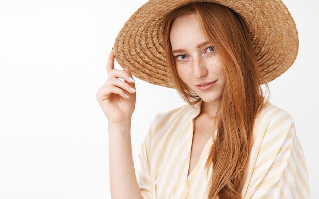 Porträt der stilvollen geheimnisvollen und sinnlichen schönen rothaarigen frau, die flirtend mit interesse und wunsch lächelnd strohhut auf kopf posierend lächelt Kostenlose Fotos