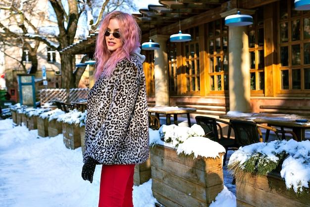 Porträt der stilvollen jungen frau, die auf der straße posiert und ungewöhnliches rosa haar, trendige leopardenjacke und vintage-brille trägt Kostenlose Fotos