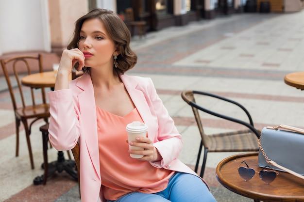 Porträt der stilvollen romantischen frau, die im café sitzt, das kaffee trinkt, rosa jacke und bluse trägt, farbtrends in der kleidung, frühlingssommermode, accessoires sonnenbrille und tasche, denkend, schauend Kostenlose Fotos