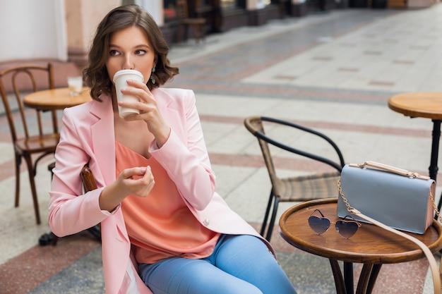 Porträt der stilvollen romantischen frau, die im café sitzt, das kaffee trinkt, rosa jacke und bluse trägt, farbtrends in der kleidung, frühlingssommermode, zubehörsonnenbrille und tasche Kostenlose Fotos