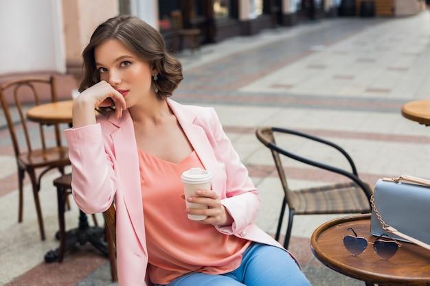 Porträt der stilvollen romantischen frau, die im café sitzt, kaffee trinkt, rosa jacke und bluse trägt, farbtrends in der kleidung, frühlingssommermode, accessoires sonnenbrille und tasche, nachdenklich Kostenlose Fotos