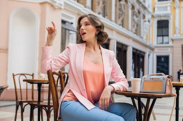 Porträt der stilvollen sinnlichen dame, die am tisch sitzt und kaffee im sommerstil der rosa jacke trinkt, blaue handtasche, accessoires, straßenart, frauenmode Kostenlose Fotos