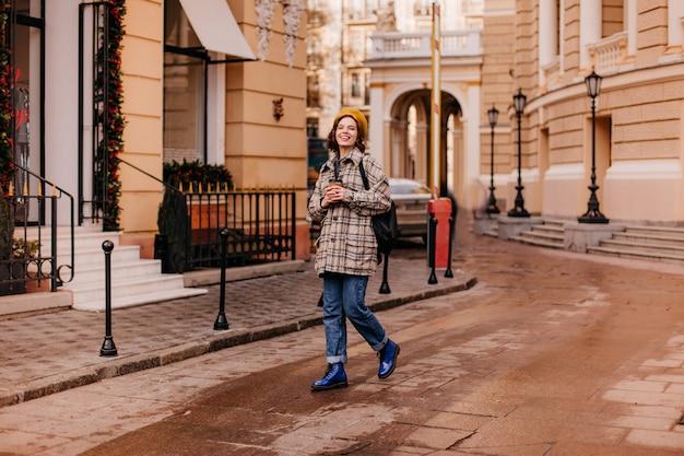 Porträt der studentin in voller länge, die im stadtzentrum geht. frau in blauen schuhen Kostenlose Fotos