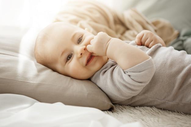 Porträt der süßen lächelnden neugeborenen tochter, die auf gemütlichem bett liegt. kind schaut in die kamera und berührt das gesicht mit ihren kleinen händen. momente der kindheit. Kostenlose Fotos