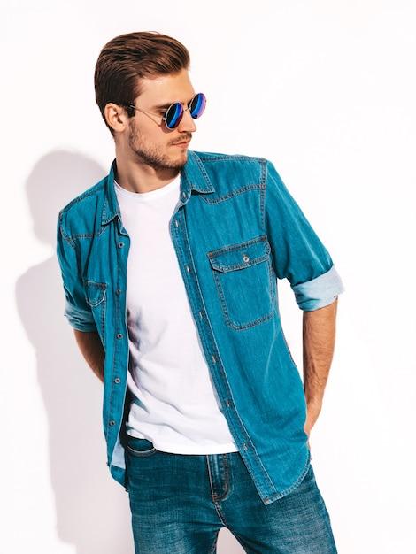 Porträt der tragenden jeanskleidung und -sonnenbrille des hübschen lächelnden stilvollen modells des jungen mannes. mode mann Kostenlose Fotos