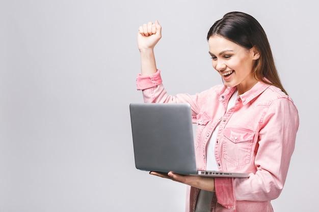 Porträt der überraschten aufgeregten lächelnden hand halten, die laptop-bildschirm betrachtet, lokalisiert über weißem hintergrund, Premium Fotos