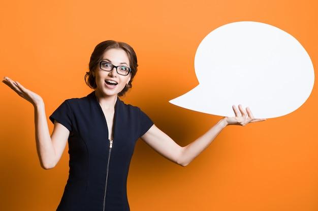 Porträt der überzeugten aufgeregten schönen jungen geschäftsfrau mit spracheblase in ihren händen, die auf orange hintergrund stehen Premium Fotos