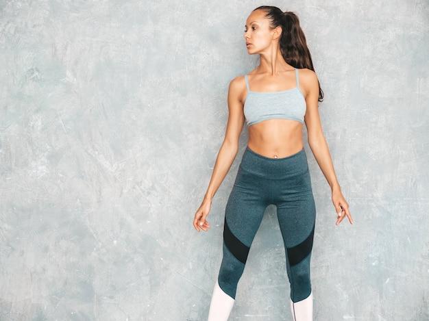 Porträt der überzeugten eignungsfrau in der sportkleidung, die überzeugt schaut frau, die im studio nahe grauer wand aufwirft Kostenlose Fotos