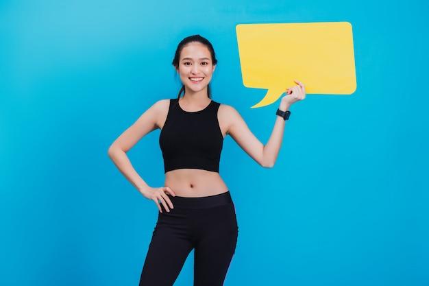Porträt der überzeugten schönen asiatischen eignungsfrau, die nach übung steht und leere gelbe blasenrede hält. Premium Fotos