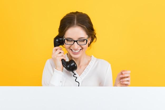 Porträt der überzeugten schönen aufgeregten lächelnden glücklichen jungen geschäftsfrau mit telefon Premium Fotos