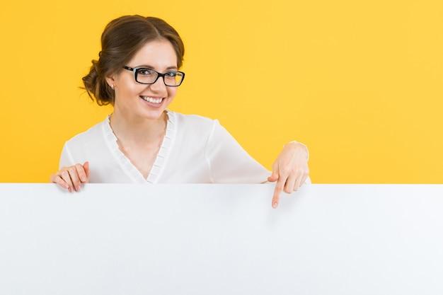 Porträt der überzeugten schönen jungen geschäftsfrau, die leere anschlagtafel auf gelbem hintergrund zeigt Premium Fotos