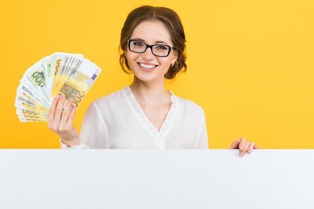 Porträt der überzeugten schönen jungen geschäftsfrau mit geld in ihren händen und in leerer anschlagtafel Premium Fotos