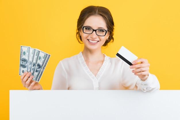 Porträt der überzeugten schönen jungen geschäftsfrau mit geld und kreditkarte in ihren händen mit leerer anschlagtafel auf gelb Premium Fotos