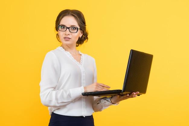 Porträt der überzeugten schönen jungen verwirrten geschäftsfrau, die an laptop auf gelb arbeitet Premium Fotos