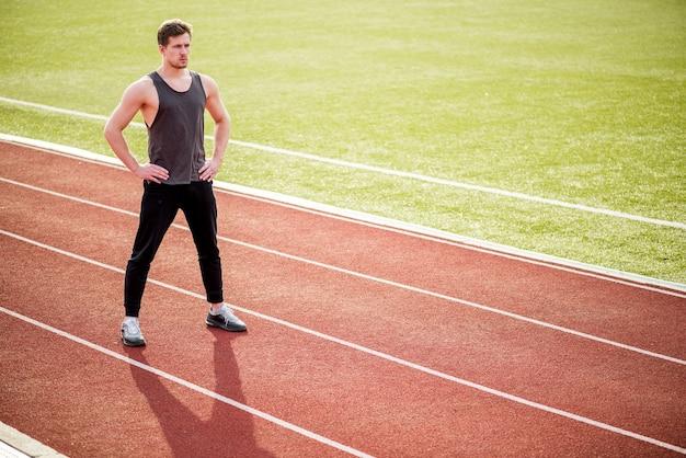Porträt der überzeugten sportperson, die auf rennstrecke steht Kostenlose Fotos