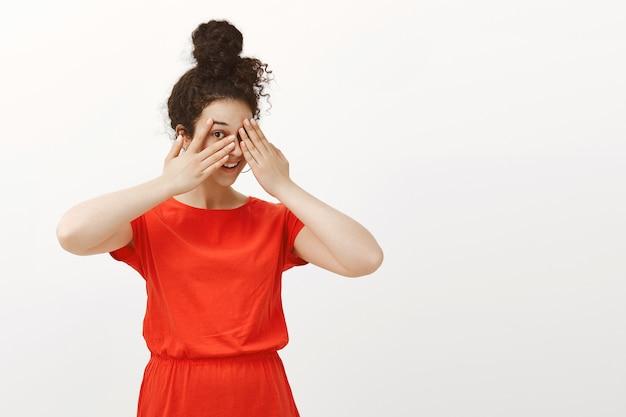 Porträt der verspielten glücklichen frau im niedlichen roten kleid mit dem im brötchen gekämmten lockigen haar Kostenlose Fotos