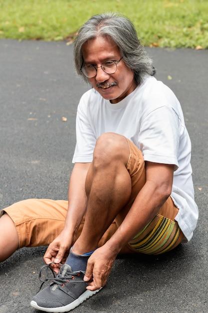 Porträt des älteren asiatischen sportmannes, der spitzee auf der straße bindet. Premium Fotos
