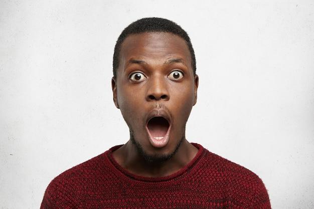 Porträt des ängstlichen jungen afroamerikanischen mannes mit bug-eyed im lässigen pullover, der vor schock schreit Kostenlose Fotos