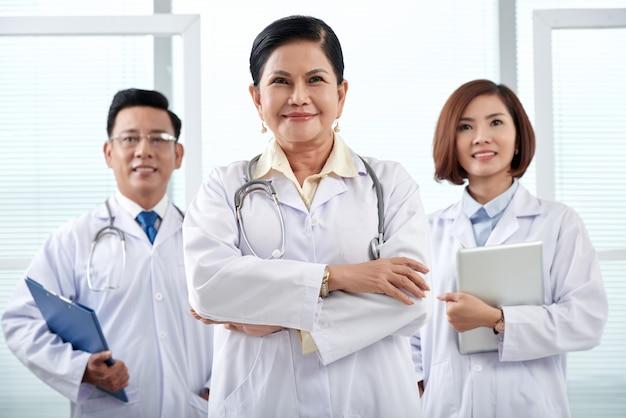Porträt des ärzteteams von drei stehend im krankenhaus, das kamera betrachtet Kostenlose Fotos