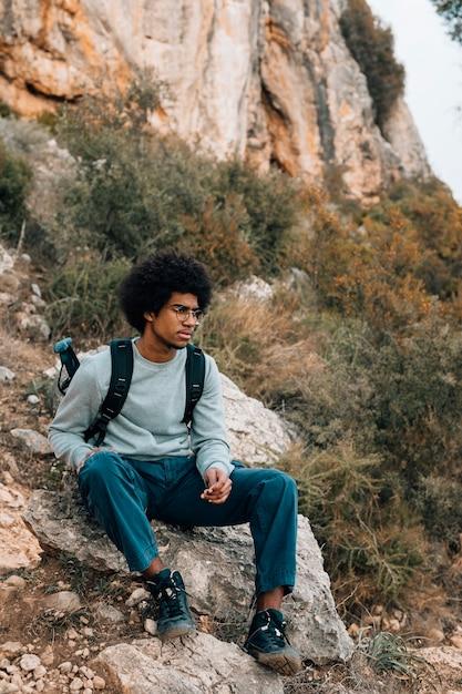 Porträt des afrikanischen jungen mannes, der auf berg sitzt Kostenlose Fotos