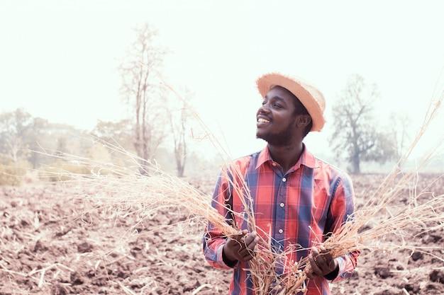 Porträt des afrikanischen landwirtmannes, der am trockenen feld steht Premium Fotos