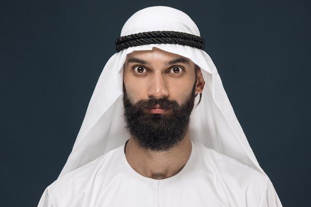 Porträt des arabischen saudi-scheichs. junges männliches modell posiert und sieht ernst oder ruhig aus. Kostenlose Fotos