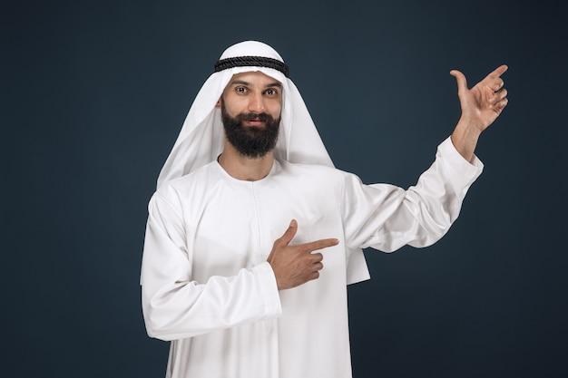 Porträt des arabischen saudischen mannes. junges männliches modell lächelnd und zeigend. Kostenlose Fotos