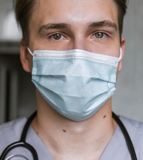 Porträt des arztes mit stethoskop und medizinischer maske Kostenlose Fotos