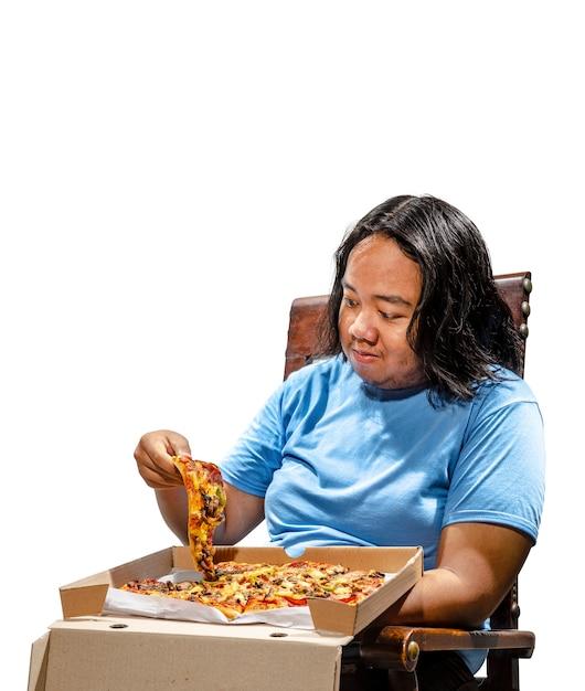 Porträt des asiatischen dicken mannes, der scheibe pizza sitzt und isst Premium Fotos
