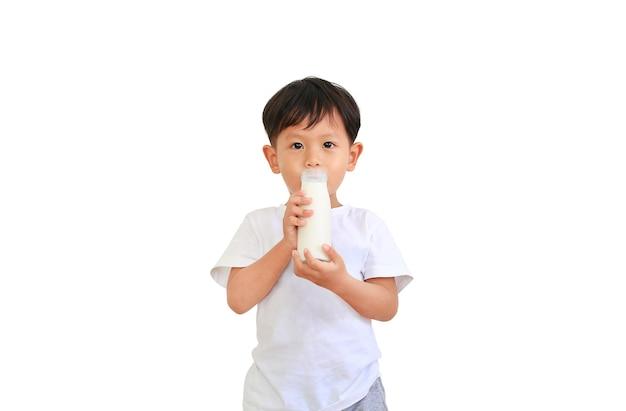 Porträt des asiatischen jungen, der milch von der glasflasche trinkt, lokalisiert auf weißem hintergrund. Premium Fotos