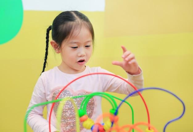 Porträt des asiatischen kindermädchens, das pädagogisches spielzeug für gehirnentwicklung am kinderraum spielt. Premium Fotos