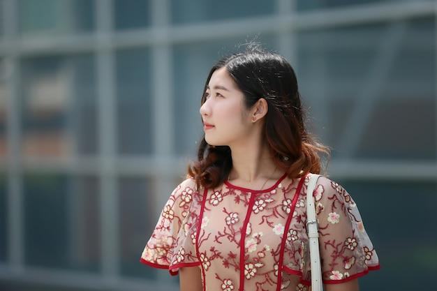 Porträt des asiatischen lächelns der jungen frau aufgeworfen Premium Fotos