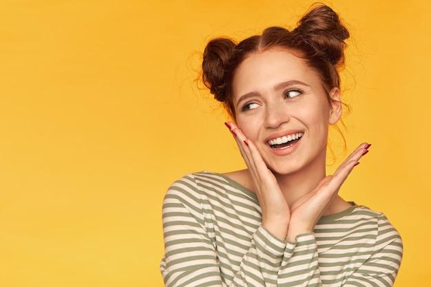 Porträt des attraktiven mädchens des roten haares mit zwei brötchen und gesunder haut. trage einen gestreiften pullover und berühre ihre wange, während du links auf den kopierplatz über der gelben wand schaust Kostenlose Fotos