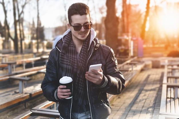 Porträt des attraktiven mannes im tragen der jacke unter verwendung des mobiltelefons und des haltens des kaffee zum mitnehmen Premium Fotos