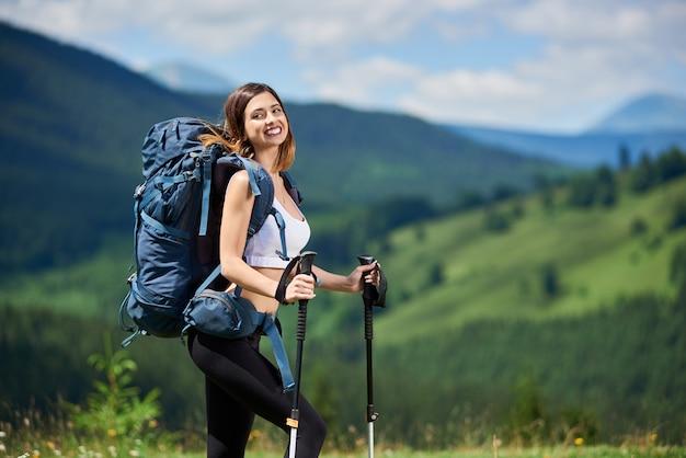 Porträt des attraktiven sportlichen weiblichen wanderers mit blauem rucksack und den wanderstöcken, lächelnd auf die oberseite eines hügels und genießen sommertag. berge, wälder und bewölkter himmel auf dem unscharfen hintergrund Premium Fotos