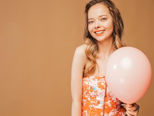 Porträt des aufgeregten jungen mädchens, das im modischen sommer colofrul kleid aufwirft. lächelnde frau mit der rosa ballonaufstellung. modell bereit für die party Kostenlose Fotos