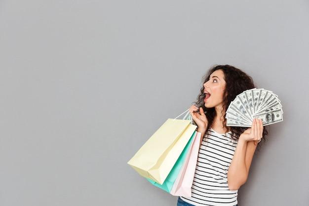 Porträt des aufgeregten weiblichen shopaholic, der mit vielen paketen und fan von dollarscheinen in den händen betrachten etwas interessanten kopienraum steht Kostenlose Fotos
