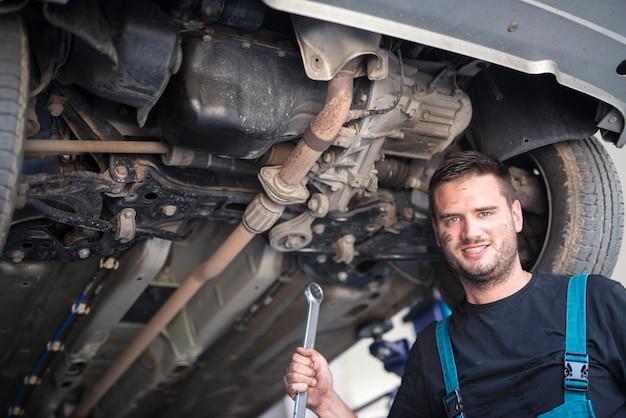 Porträt des automechanikers mit dem schlüsselwerkzeug, das unter dem fahrzeug in der autowerkstatt arbeitet Kostenlose Fotos