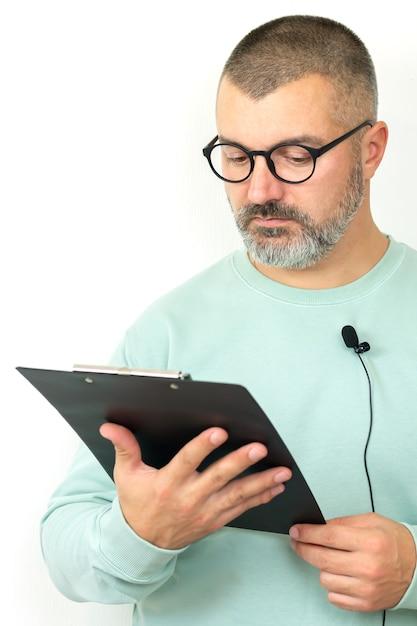 Porträt des bärtigen geschäftsmannkutschers, der brille mit mikrofon und zwischenablage trägt. mentor sprecher hält online-lektion Premium Fotos