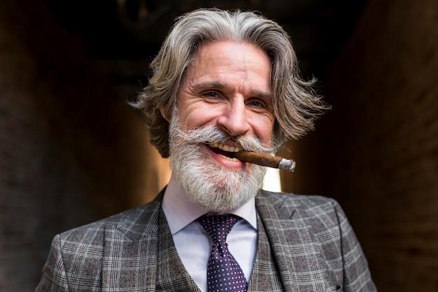 Porträt des bärtigen reifen männlichen rauchens Kostenlose Fotos