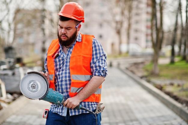 Porträt des bartarbeitskraftmann-klagenbauarbeiters im orange sturzhelm der sicherheit gegen pflasterung mit eckiger schleifmaschine in der hand. Premium Fotos