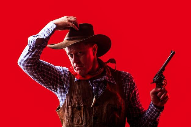 Porträt des bauern oder des cowboys im hut. amerikanischer bauer. porträt des mannes, der cowboyhut, waffe trägt Premium Fotos