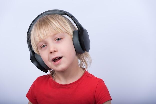 Porträt des blonden jungen mit kopfhörern Premium Fotos