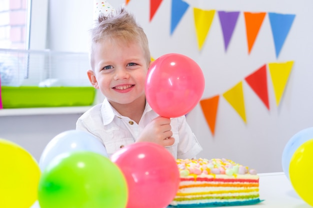 Porträt des blonden kaukasischen jungen, der an der kamera nahe geburtstagsregenbogenkuchen lächelt. festlicher bunter hintergrund mit ballonen Premium Fotos