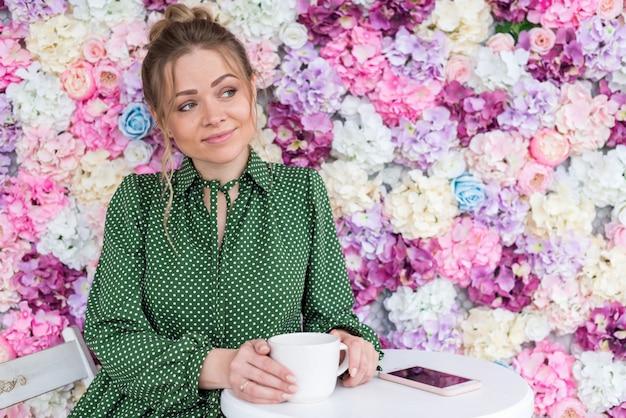 Porträt des blonden mädchens sitzt am tisch im café gegen einen blumenhintergrund mit tasse tee Premium Fotos