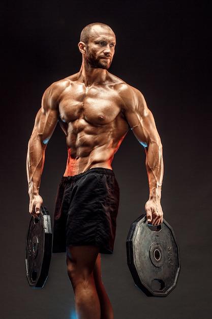 Porträt des bodybuilders mit dummköpfen in seinen armen auf grauem backg Premium Fotos