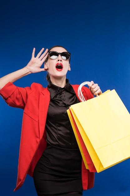 Porträt des brunettemädchens in der sonnenbrille mit taschen in den händen Premium Fotos