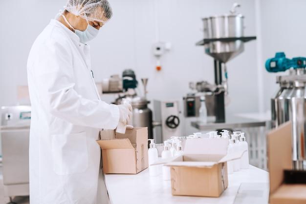 Porträt des chemiearbeiters in sterilen gleichmäßigen verpackungsflüssigkeitsseifen in kisten Premium Fotos